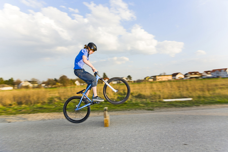 boy jumping with his dirtbike over a ramp at the street photo