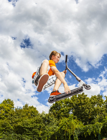 boy going airborne with his push scooter Imagens