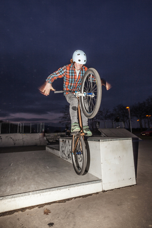 young boy jumps with his dirtbike in the skate park over a ramp photo