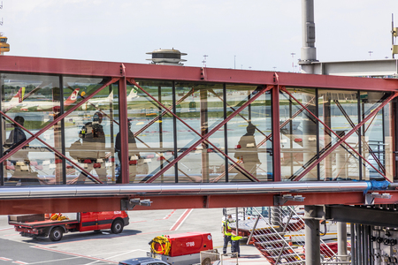 HAMBURG, GERMANY - MAY 17, 2017: people boarding via passenger Bridge in Haburg to the aircraft in Terminal 2.  Hamburg is a major Hub with 36 Mio passengers per year in Germany. Publikacyjne