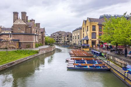 Cambridge, UK - APR 16, 2017: People enjoying a rainy spring day, punting in river Cam in Cambridge UK