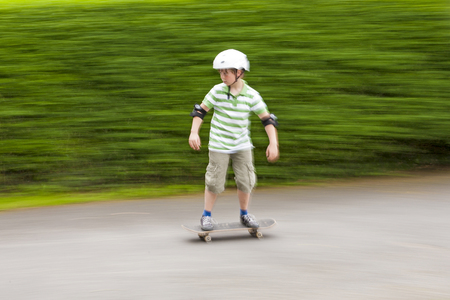 boy skating with speed with green blurred background photo
