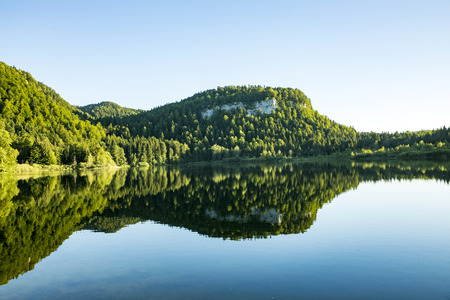 scenic reflection of Forest in the clear lake at Bonlieu in the french Jura region