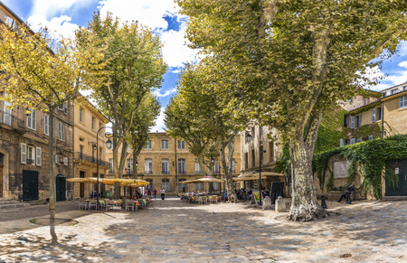 AIX EN PROVENCE, FRANCE - AUG 11, 2017: people enjoy resting at a tree covered place in the  old town of charming Aix en Provence. The old roman city was in former times the capital of the provence.