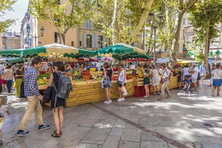 AIX EN PROVENCE, FRANCE - 2017 년 8 월 17 일 : 사람들은 엑상 프로방스의 식품 시장에서 쇼핑하러갑니다. 현지 농부는 시장에서 신선한 채소와 과일을 제공합