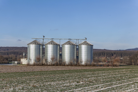 four silver reflecting silos in winter landscape Stock Photo