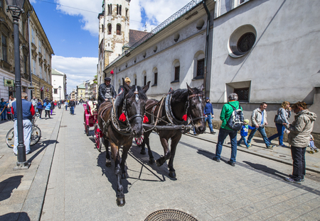 KRAKOW, POLAND - MAY 4, 2014: Horse-drawn carriage at the Market Square, standardized the color, total length of no more than 7.0 m, can be harnessed to a max of two horses  in Krakow, Poland. Banco de Imagens - 85595386