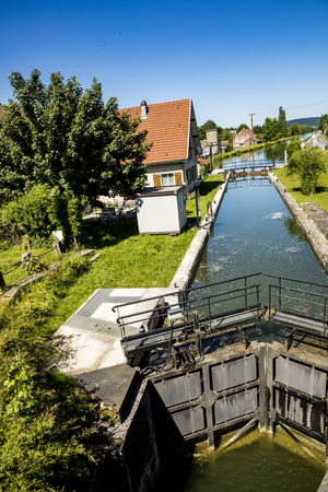 COLUMBIER-FONTAINE, FRANCE - JUNE 10, 2017: sluice at river doubs in France with old house