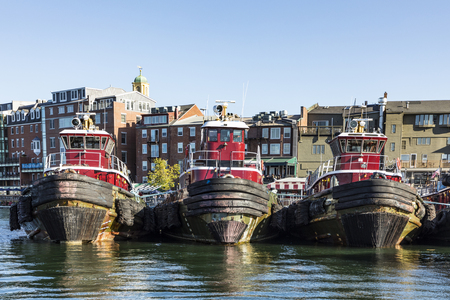 PORTSMOUTH, USA - SEP 27, 2017:  tug boats anker in row in front of harbor building. The old harbor buildings in background were changed to modern apartments after year 2000.
