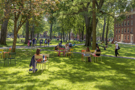 CAMBRIDGE, MA, USA - SEPTEMBER 13, 2017: Students and tourists rest in lawn chairs in Harvard Yard, the open old heart of Harvard University campus  in Cambridge, MA, USA.