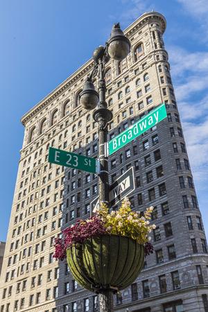 NEW YORK, USA - OCT 5, 2017: Flatiron building on Manhattan with street sign Broadway. A 22-storied building was designed by Chicago architect Daniel Burnham in 1902.
