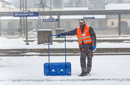 WIESBADEN, GERMANY - DECEMBER 12: Worker is cleaning the train platform from snow in heavy snowstorm  to prevent accidents on December 12, 2010 in Wiesbaden, Germany.