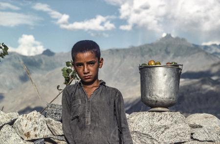 GILGIT, PAKISTAN - JUNE 30, 1986: local farmer boy takes home the picked ripe tomatos. Children have to help in the smaller farms. Editorial