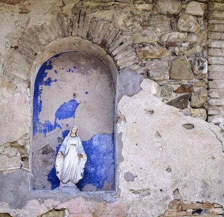古い教会の遺跡にある聖母マリアの小さな彫像 写真素材