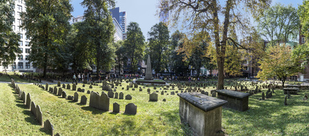 BOSTON, USA - SEP 12, 2017: Rows of headstones under a tree at Granary Burial Ground. It became a cemetery in 1660 the third oldest in the town of Boston, Massachusetts. Editorial