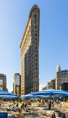 NEW YORK, USA - OCT 5, 2017: people enjoy sitting at broadwayon public chairs with free wlan and looking to the spectacular facade of Flatiron building.