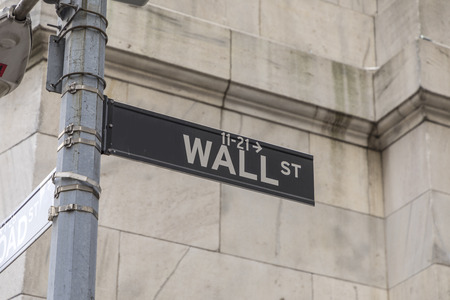 NEW YORK, USA - OCT 5, 2017: Wall street sign in lower  Manhattan with history of New York stock exchange and man in black. Editorial