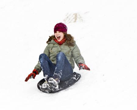girl has fun by sledging down the snowy hill while it is snowing