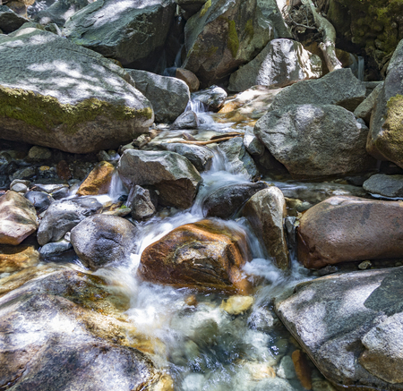 colorful stones in the clear cold water of a creek with water from yosemite waterfall