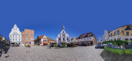 WOLGAST, GERMANY - AUG 13, 2015: people enjoy gothic St Petri church in Wolgast under blue sky with historic market place. Editorial