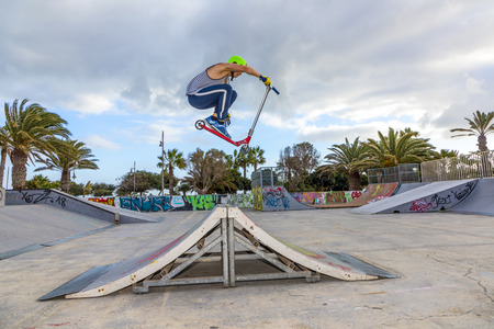 ARRECIFE, SPAIN - JAN 18, 2018: teenage boy jumping at the skate park over a ramp. The skate park is painted with grafitty by young people.