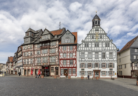 BUTZBACH, GERMANY - MAR 30, 2018: people on a sunny day at the old historic market place with half timbered houses in Buedingen. Editorial