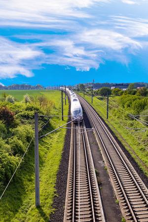 RAUNHEIM, GERMANY - APR 21, 2018: german high speed train Intercity Express (ICE) train of Deutsche Bahn passes rural landscape near Raunheim. ICE 3 class train is manufactured by Siemens.