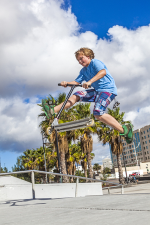 boy with scooter is jumping at the skate park Stock Photo