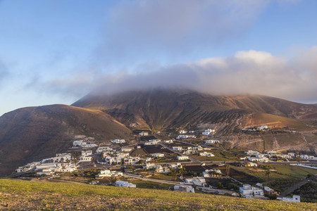 village of Femes in Lanzarote in morning fog with blue sky Stock fotó