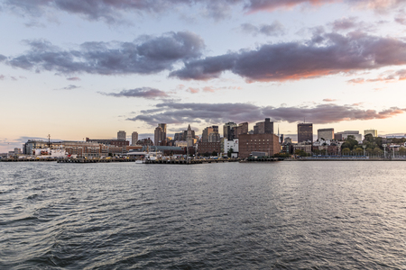 view to skyline of Boston in sunset with pier