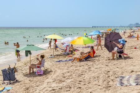 SUNNY ISLES BEACH, USA - AUG 17, 2014: people enjoy and relax near the pier in Sunny Isles Beach, USA. In 1936, Milwaukee malt magnate Kurtis built the Sunny Isles beach and pier. Editoriali