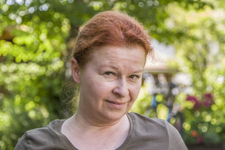 portrait of woman with red hair in the garden 스톡 콘텐츠 - 107390730