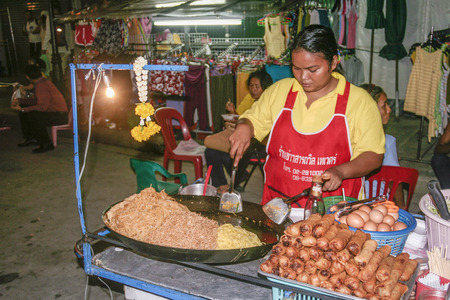 BANGKOK, THAILAND - DEC 3, 2006: woman at the street sells fresh noodles, eggs, soja beans with salad at a movable food stall in Bangkok by night. The selling  licence is controlled by government.