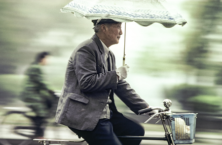 BEIJING, CHINA - AUG 1, 1982: old man rides his bicycle with umbrella in his arm. I 1982 bicycle was for more than 95 percent of chinese people the way for transportation even in Beijing.