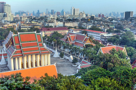 BANGKOK, THAILAND - DEC 2, 2006: aerial view to Wat Thepthidaram with skyline of Bangkok in background. Thailand is a buddhistic country.