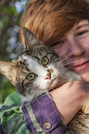 boy hugging with his cute young cat Фото со стока