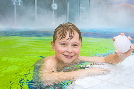 children having fun in the outdoor thermal pool in wintertime