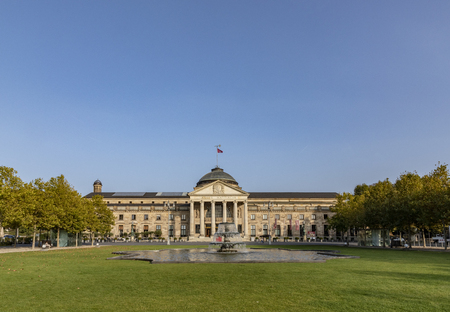 WIESBADEN, GERMANY - OCT 18, 2018: old Kurhaus in Wiesbaden with green park and fountain in foreground. The Kurhaus servves as casino nowadays.