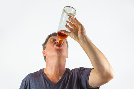 man drinking alcohol out of a bottle Standard-Bild