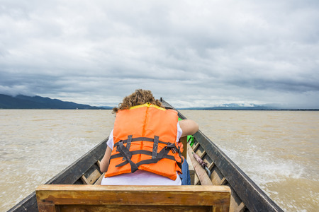 female tourist in water taxi at Inle lake in cloudy weather