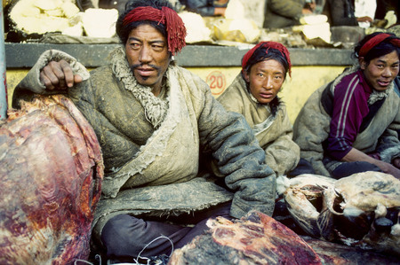 LHASA, CHINA - DEC 20, 1984: local people from the hills meet in the old part near the Jokhan palace in Lhasa, China. They sell meat on open air butchery. Editorial