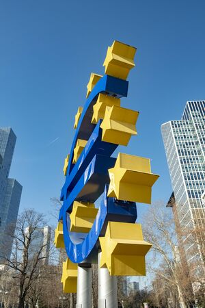 FRANKFURT, GERMANY - FEB 26, 2019: Famous euro sign in Frankfurt am Main under blue sky. At the background is the skyscraper of the european central Bank (ECB).
