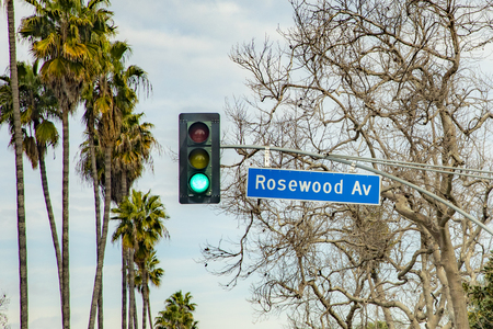 street name Rosewood Avenue in Hollywood with red traffic light under cloudy sky Stock Photo
