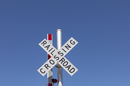 railroad crossing sign under clear blue sky