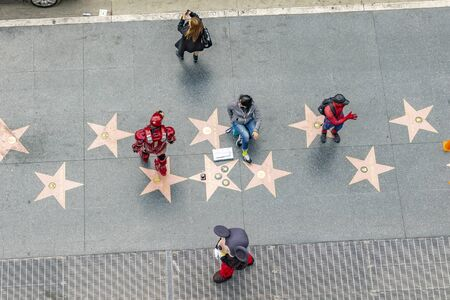 LOS ANGELES, USA - MAR 5, 2019: aerial of walk of fame with tourists looking for stars and actors earning money by posing for movie figures.