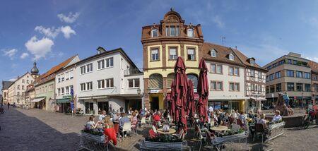 MARKTHEIDENFELD, GERMANY - MAR 30, 2019:  people enjoy a warm summer das at the historic central market place in Marktheidenfeld, Germany.