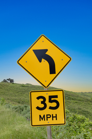yellow street sigh 35 MPH at Cabrillo highway with sign winding road under blue sky Stock Photo - 122950098