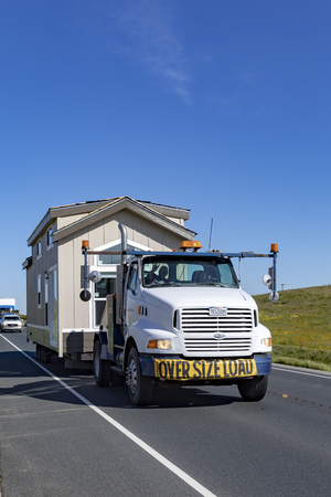 Bridgeport, USA - MAR 11, 2019: people transport their home by truck from one mobile home village to the next.
