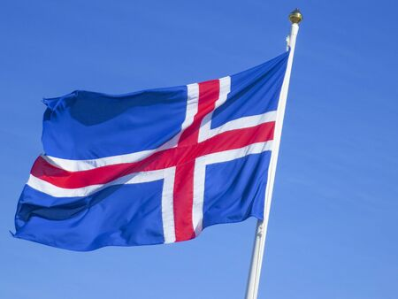 icelandic flag in wind under clear blue sky Zdjęcie Seryjne