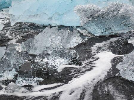 Incredible pieces of the iceberg sparkle on famous Diamond Beach at Jokulsarlon lagoon during sunset